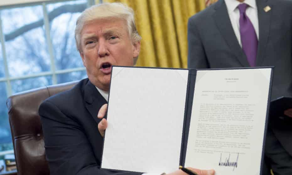 President Donald Trump with an executive order withdrawing the US from the Trans-Pacific Partnership.
