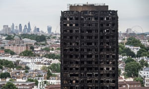 The remains of Grenfell Tower stand with the City of London in the background