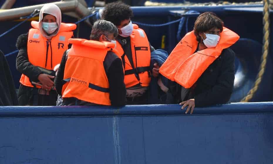 Rescued migrants wearing orange life jackets on a UK Border Force boat