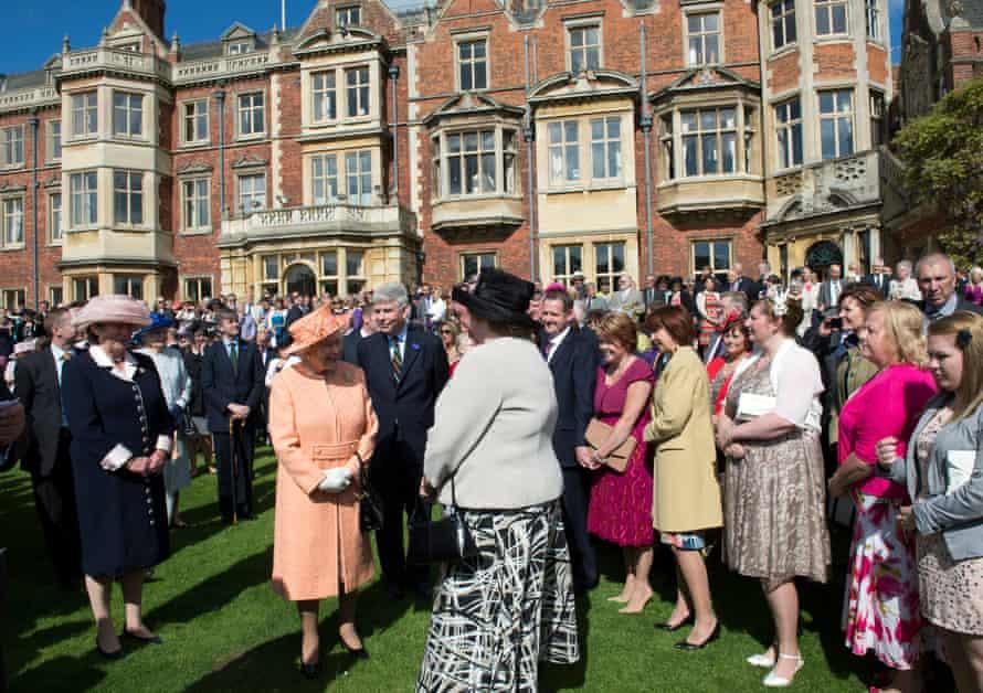 Queen Elizabeth II resplendent in apricot, hosts a garden party at the Sandringham Estate in Norfolk in 2012.