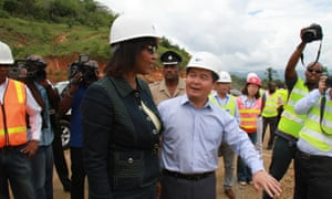 Chinese ambassador to Jamaica Dong Xiaojun shows Portia Simpson around the North/South Highway construction site in Linstead, Jamaica, on 20 May 2014.