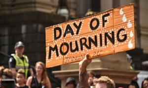 """A protester holds up a sign during an """"Invasion Day"""" rally on Australia Day in Melbourne on January 26, 2018."""