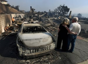 Michael and Vonea McQuillam stand beside their former home destroyed by the Thomas fire in Ventura