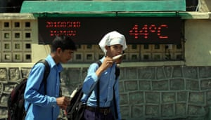 School children eat ice-cream as they walk past a display recording a temperature of 44C in Jammu, Kashmir