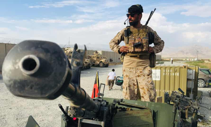 An Afghan soldier keeps watch on a Humvee tank after US forces left Bagram airfield on 5 July