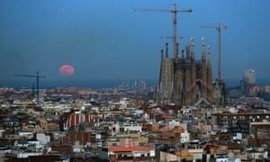 A full moon rises over the Mediterranean sea behind Barcelona.