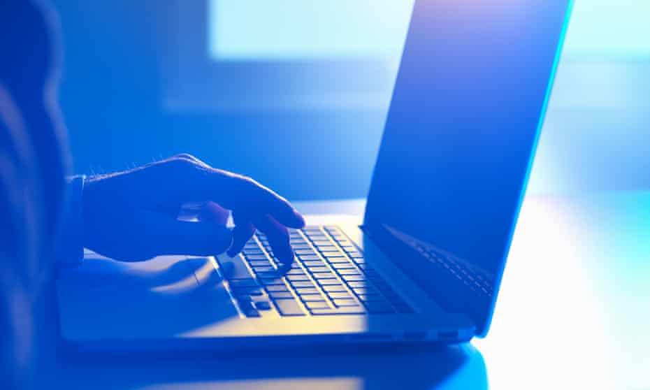 A man typing on a laptop
