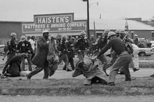 John Lewis (in foreground) is beaten by a state trooper as they break up the march in Selma. Lewis suffered a fractured skull.<br>