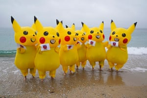 Protesters dressed as Pikachu characters demonstrate on Gyllyngvase beach in Falmouth, calling on the Japanese government to stop burning coal by 2030