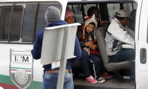 A migrant family waits before being transported by Mexican authorities to the San Ysidro port of entry to begin the process of applying for asylum in the US.