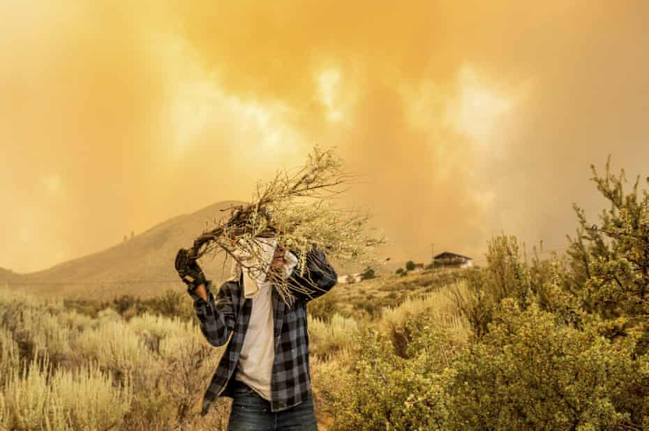A California man clears a fire break around his home as the Beckwourth Complex fire burns in the north-east of the state.