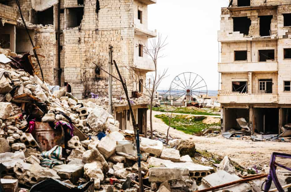 An abandoned ferris wheel and bombed buildings in the town of Ariha.
