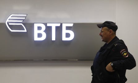 A police officer stands guard near a sign with the logo of the Russian lender VTB in Moscow