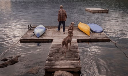 A rear view of William Wegman and his two Weimaraners, Flo and Topper, standing on a jetty in the lake