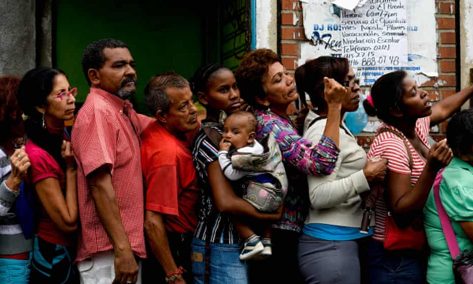 People queue to buy food and basic household items in the Petare neighbourhood of Caracas.