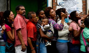 People queue up to buy food and basic household items in a supermarket in Caracas on 16 July 2016.