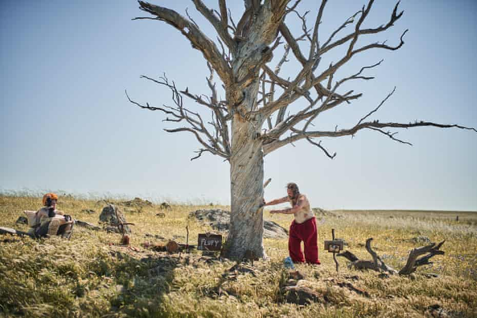 a child and a dirty man in santa pants near a big old dead tree