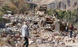 People walk on the rubble of a house destroyed by an airstrike in Sana'a in Yemen
