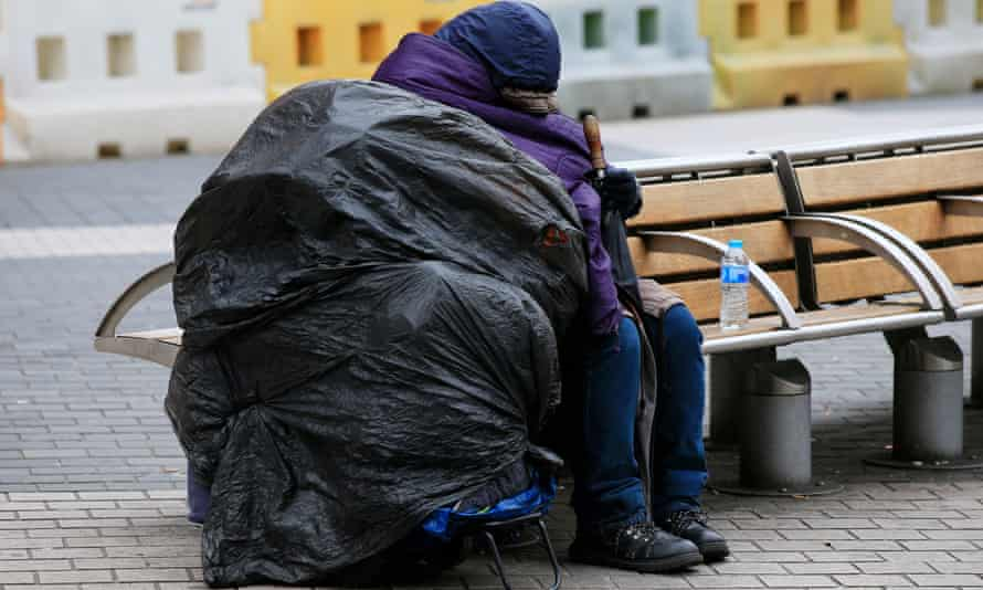 Homeless person resting on a bench