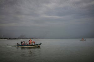 Boats carry papier-mache statues of Ganesh