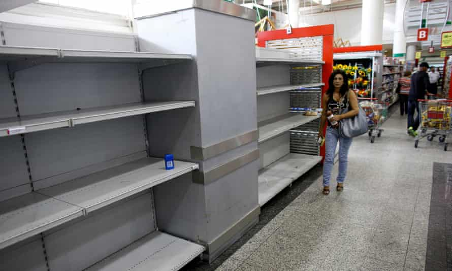 A woman walks past empty shelves where toilet paper should be displayed in a supermarket in Caracas.