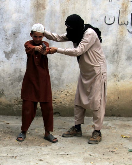 Am Islamic State militant shows a child how to use a gun in Kunar province, Afghanistan.