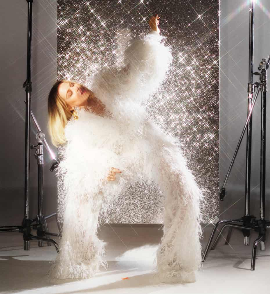 Kylie Minogue wearing a white feather jumpsuit. Stylist: Karl Willett. Hair and makeup: Christian Vermaak. Manicurist: Adam Slee. Set design: Paulina Piipponen. Stylist's assistant: Adele Pentland. Jumpsuit by Ashi Studio. Earrings by Civilian London. Main image: top and gloves by Alistair James.