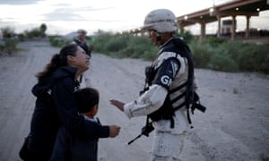 A Guatemalan migrant and her son ask a member of the Mexican national guard to let them cross in the US, as seen from Ciudad Juárez, Mexico, on 22 July.