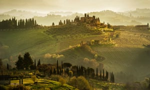 Vineyards and rolling hills below a cluster of houses near San Gimignano in the early morning.<br>San Gimignano, Tuscany, Italy.