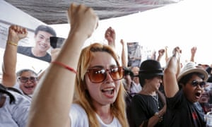 Members of the New Democracy Movement activist group and supporters of the 14 students celebrate outside the military court in Bangkok.