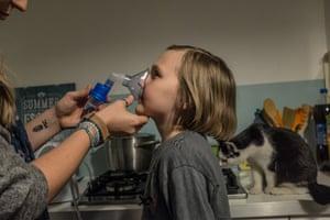 Eva Ciesielska assists nine-year-old Zoe with a nebuliser