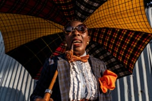 Nkodia Aurelie, 48-year-old businesswoman and sapeuse for 36 years, in Brazzaville. Dressed in flamboyant $2,000 (£1,500) outfits complete with bow ties, fedoras and umbrellas, the sapologists strut their stuff across dirt roads in 40-degree heat. The gross national income per capita in the Democratic Republic of the Congo, on the opposite bank of the Congo river from Brazzaville, was $900 in 2018, which puts the purchase of $1,300 crocodile-skin shoes into perspective