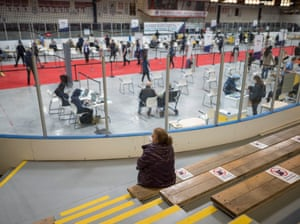 A person waits in the bleachers as workers administer vaccinations at the Downsview arena vaccination site, in Toronto, Canada.