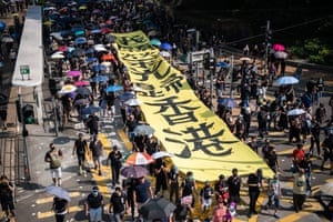 Protesters carry a banner referring to the song Glory to Hong Kong on Tuesday.