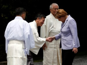 German chancellor Angela Merkel is welcomed by Shinto priests as she visits the Ise grand shrine