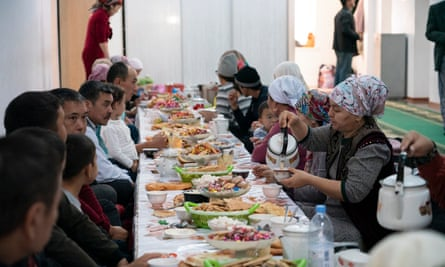 Pilgrims at a long table filled with food and passing teapots