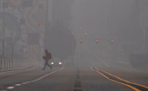 A man crosses a street in downtown Portland, Oregon where air quality due to smoke from wildfires was measured to be amongst the worst in the world, September 14, 2020