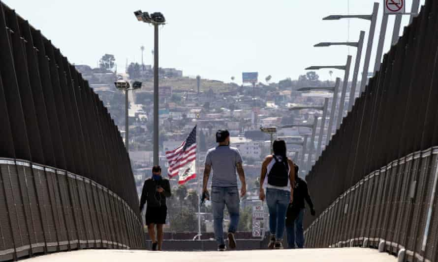 People wearing face masks cross the bridge over the freeway at the US-Mexico border in San Diego, California.