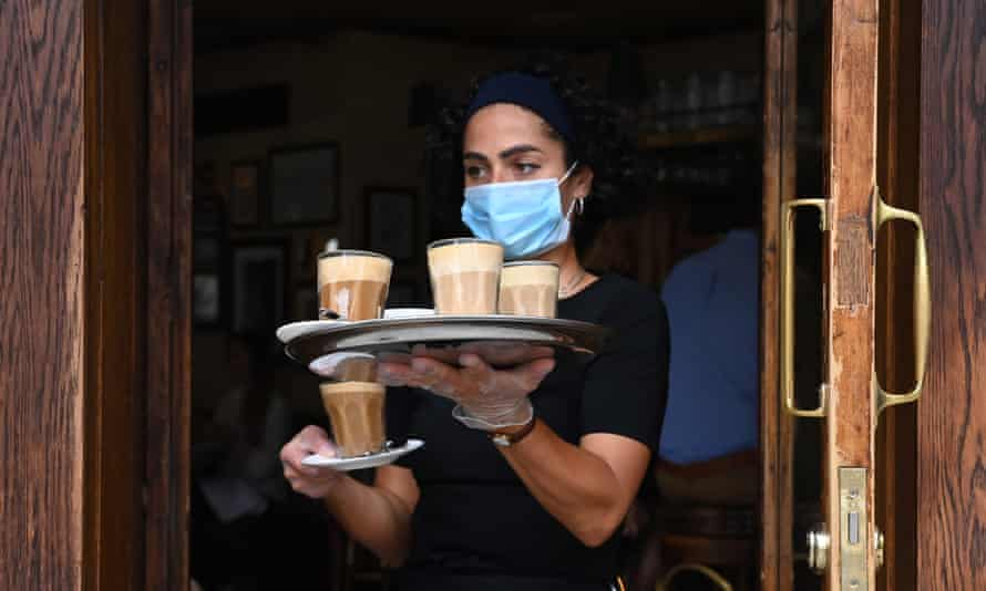 A waitress serves coffees in a bar in Soho, central London, July 2020.