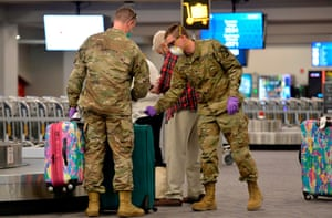 US Army National Guard soldiers assist elderly travellers with their luggage at TF Green International Airport in Warwick, Rhode Island. Any person entering the state of Rhode Island to self-quarantine for 14 days.