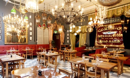 The dining room with tiled floor, small wooden tables and fancy chandeliers