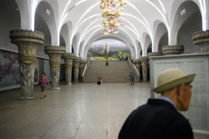 A commuter reads a newspaper on the platform of a subway station in Pyongyang.