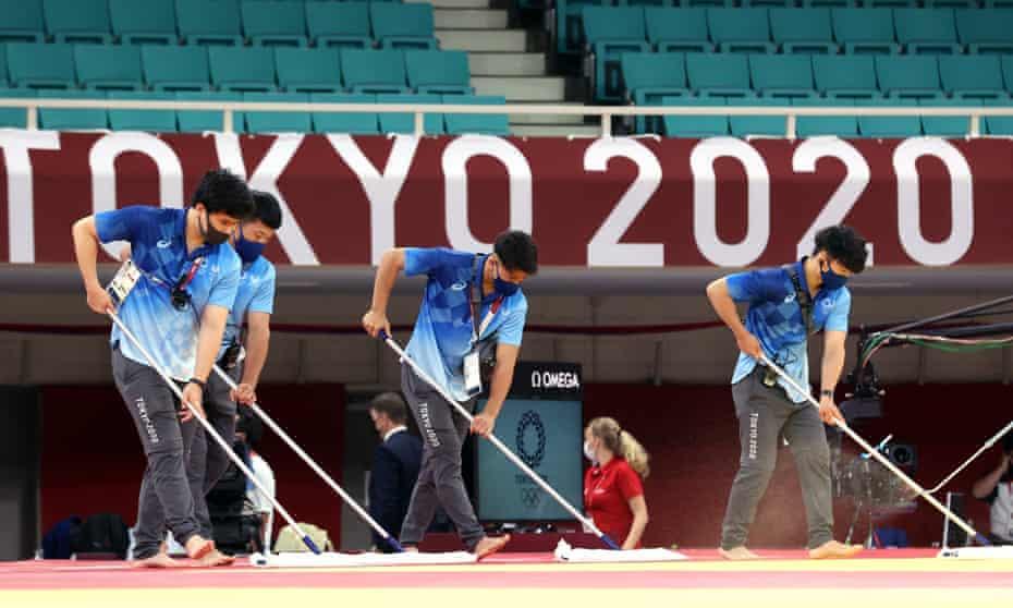 Technicians clean the floor of the judo arena
