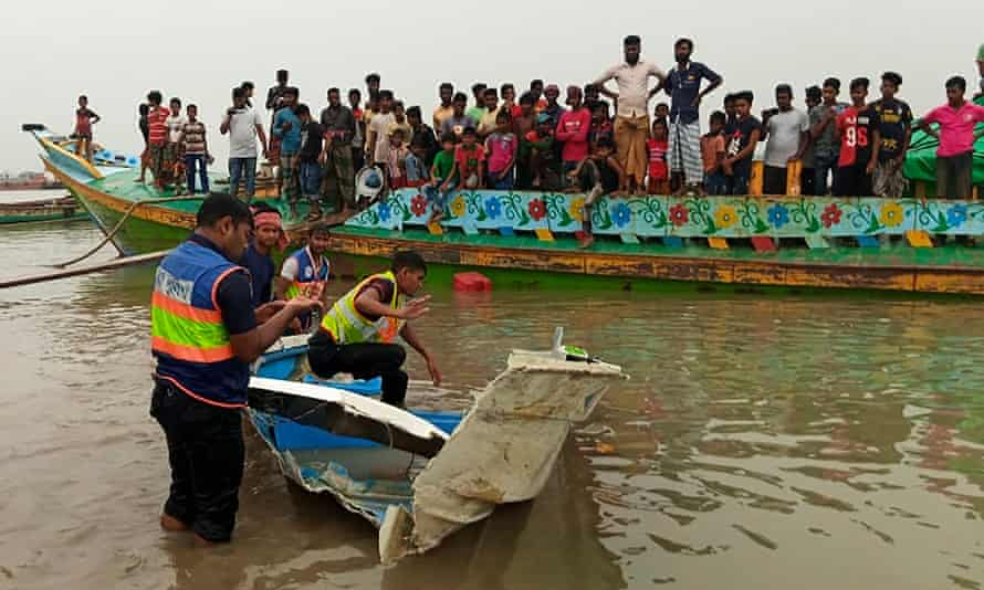 Bangladeshi police inspect a broken section of the speedboat that collided with a vessel transporting sand.