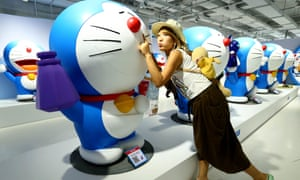 A girl poses for photos with figures of Doraemon