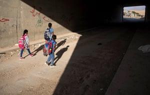 Bedouin students walk under a bridge to their school  in Khan al-Ahmar, West Bank
