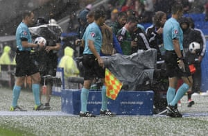 Referee Pavel Kralovec walks off the pitch during a hailstorm in the match between Ukraine and Northern Ireland at the Stade de Lyon.