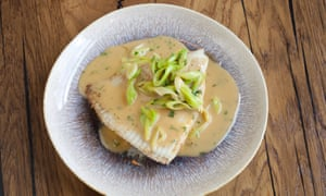 Skate wing in a buttery sauce on a round plate
