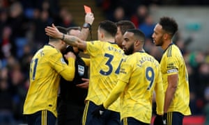 Arsenal's Pierre-Emerick Aubameyang is shown a red card by referee Paul Tierney after a referral to VAR.