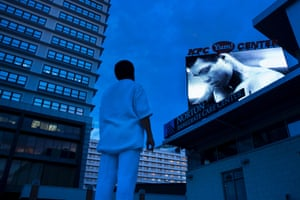 A man watches a slide show of Muhammad Ali photos displayed on a screen on Thursday, outside the KFC Yum! Center, where mourners will attend a memorial service for the boxing legend